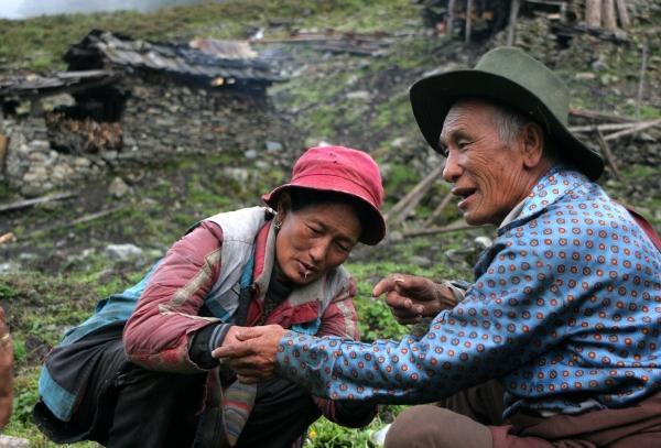 Женщина из кочевья зашивает дедушке рукав